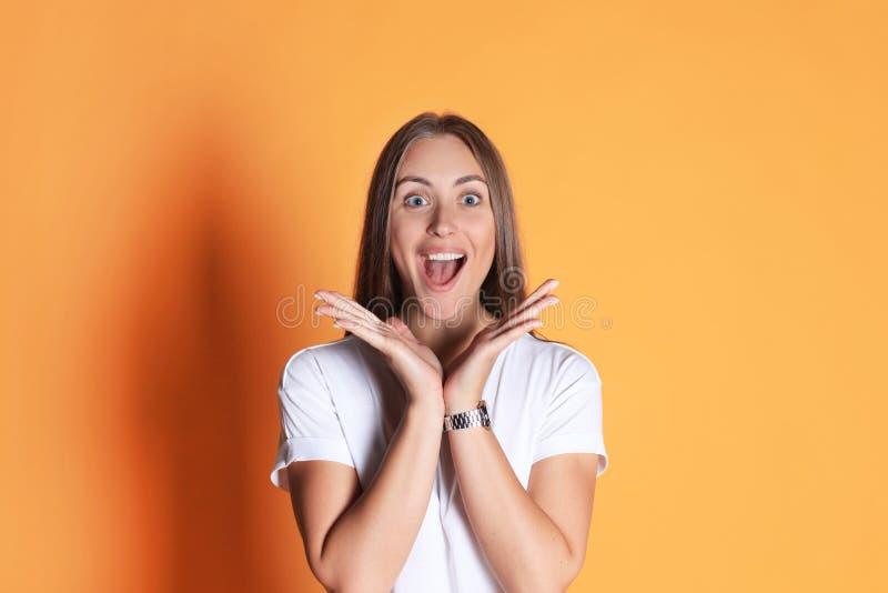 Giovane donna in abbigliamento casuale che si domanda e che grida sopra il fondo giallo fotografia stock