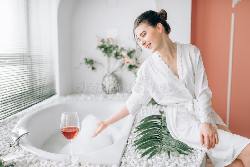 Giovane donna in accappatoio bianco di n, interno del bagno fotografia stock libera da diritti