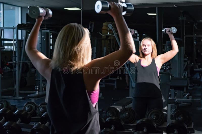Giovane donna adatta alla palestra che fa esercizio heavylifting con la barra immagine stock