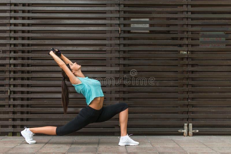 Giovane donna adatta che allunga facendo esercizio basso di affondo di yoga all'aperto sulla via della città fotografia stock