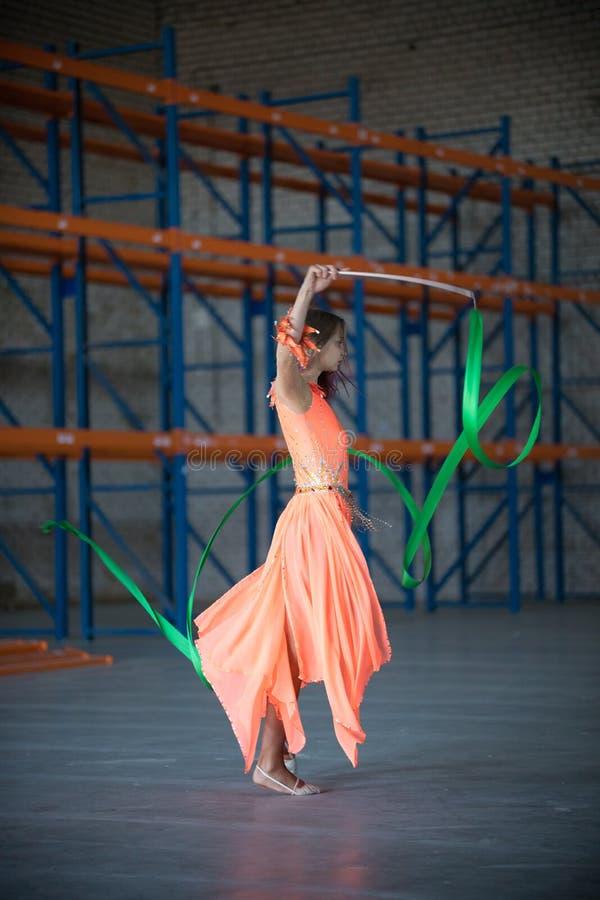 Giovane donna adatta che balla con il nastro relativo alla ginnastica in mani all'interno immagini stock libere da diritti