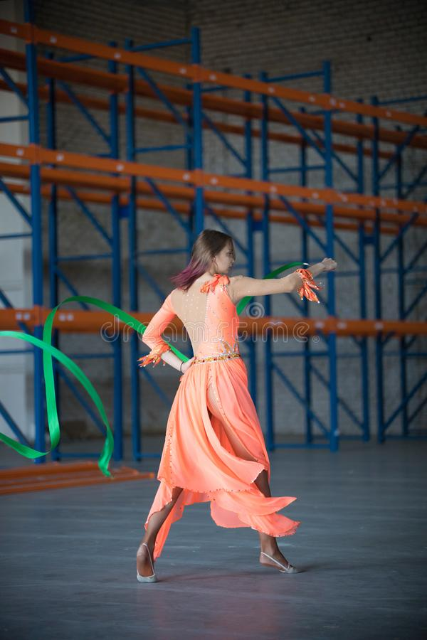 Giovane donna adatta che balla con il nastro relativo alla ginnastica in mani nel magazzino fotografia stock