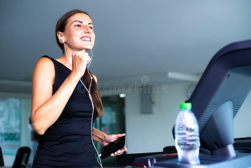 Giovane donna adatta che corre sulla pedana mobile che ascolta la musica tramite cuffia alla palestra fotografie stock