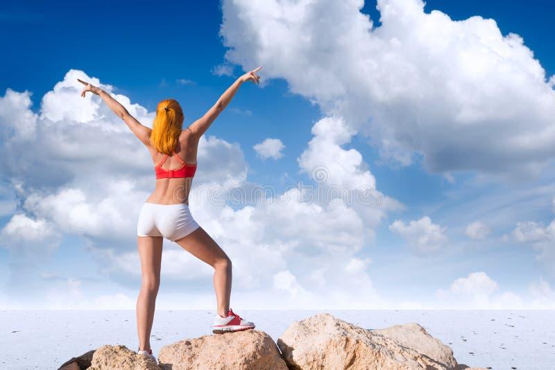 Giovane donna adatta con le mani sollevate sopra il deserto fotografia stock libera da diritti