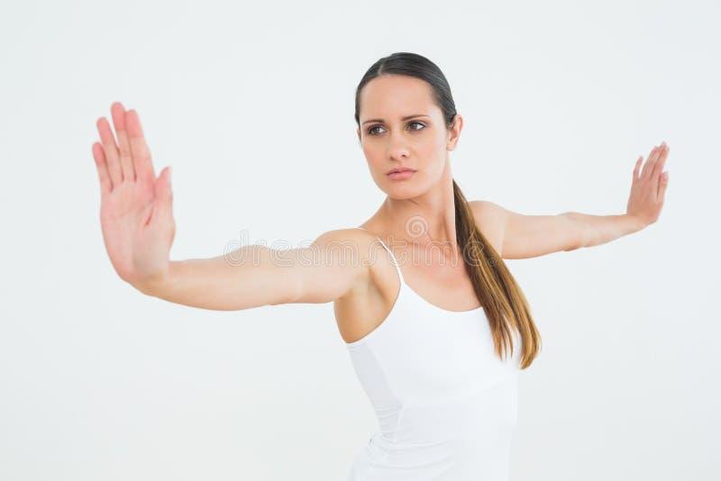 Giovane donna adatta concentrata che fa gli esercizi di pilate fotografie stock