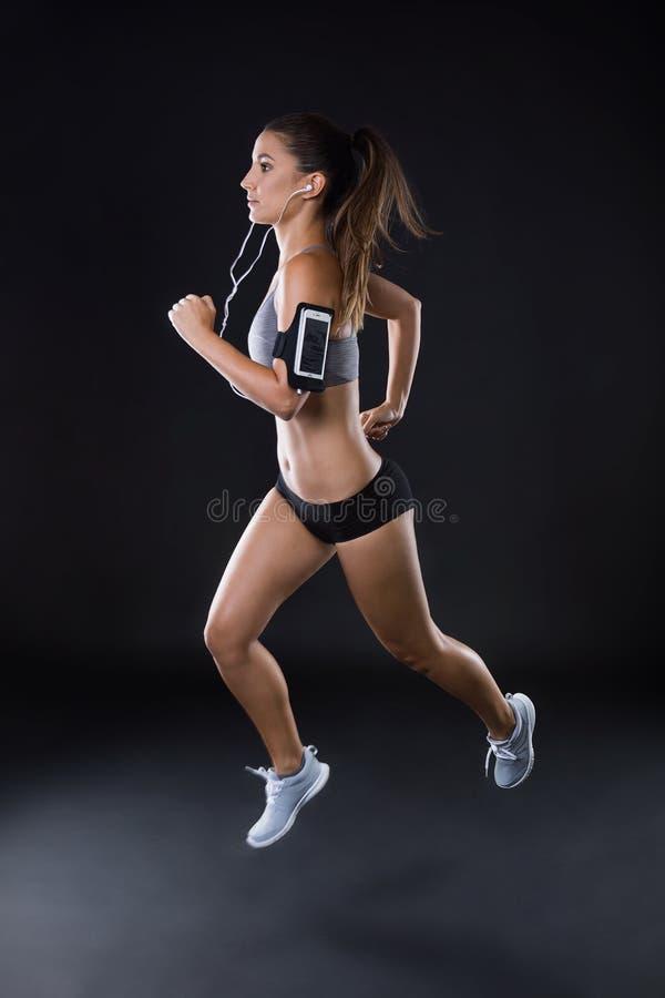 Giovane donna adatta e sportiva che investe fondo nero immagini stock libere da diritti