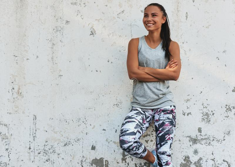 Giovane donna adatta felice che sorride durante una pausa all'aperto che sta contro il muro di cemento Riposo femminile atletico  immagini stock