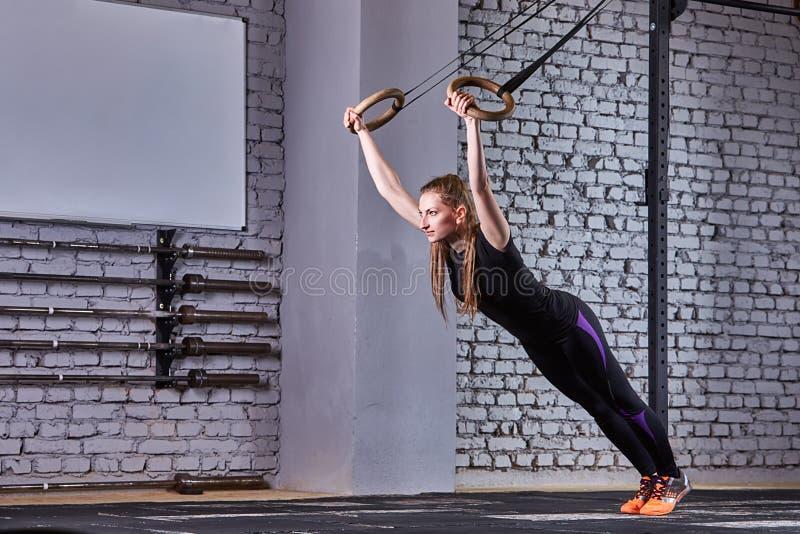 Giovane donna adatta nello sportwear nero che si esercita con gli anelli relativi alla ginnastica in palestra contro il muro di m fotografia stock libera da diritti