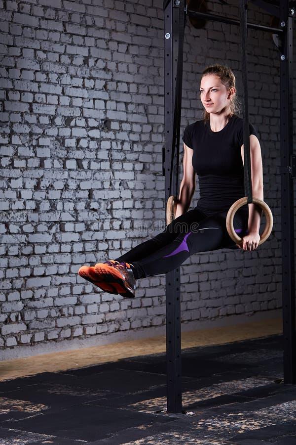Giovane donna adatta nello sportwear nero che si esercita con gli anelli relativi alla ginnastica in palestra contro il muro di m immagini stock