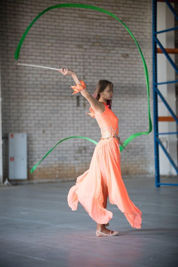 Giovane donna adatta in vestito arancio che balla con il nastro relativo alla ginnastica in mani all'interno fotografia stock libera da diritti