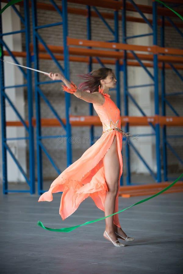 Giovane donna adatta in vestito arancio che balla con il nastro relativo alla ginnastica in mani nel magazzino immagini stock