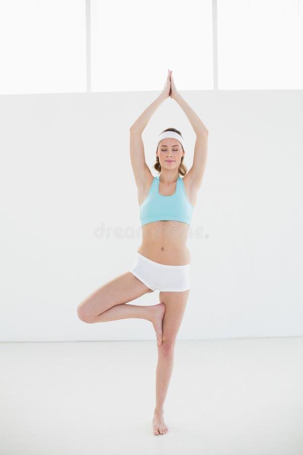Giovane donna adorabile che fa posa di yoga dell'albero nella palestra fotografia stock