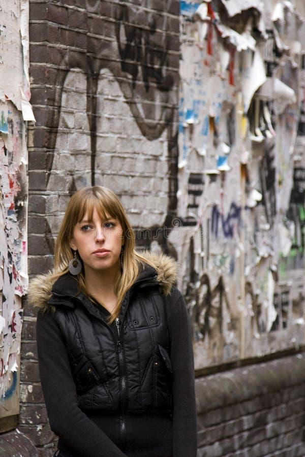 Giovane donna adulta che si leva in piedi contro la parete fotografie stock