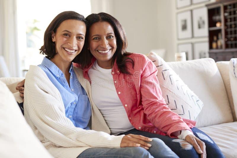 Giovane donna adulta che si siede sul sofà in salone con sua madre che sorride alla macchina fotografica fotografia stock libera da diritti