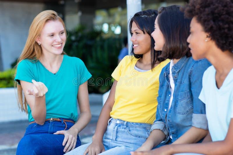 Giovane donna adulta con capelli rossi che parla con le amiche immagini stock