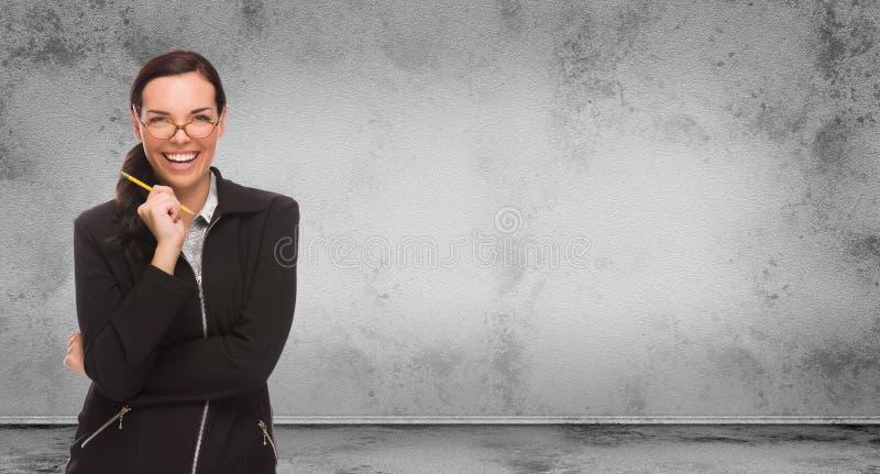 Giovane donna adulta con la matita ed i vetri che stanno davanti alla parete in bianco Grungy in bianco con lo spazio della copia immagini stock