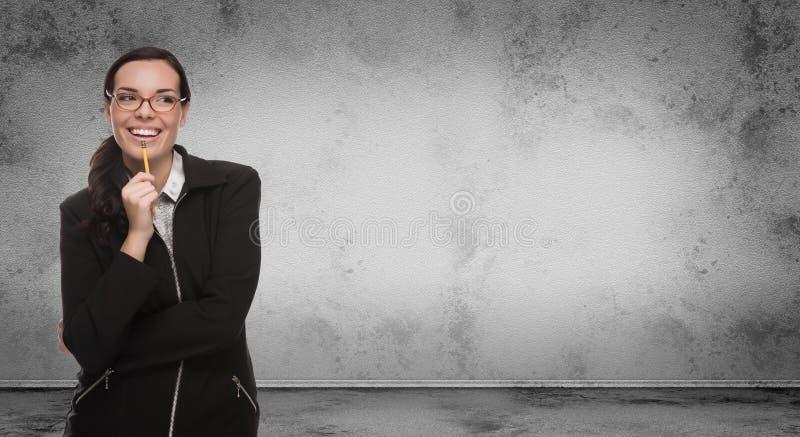 Giovane donna adulta con la matita ed i vetri che stanno davanti alla parete in bianco Grungy in bianco con lo spazio della copia fotografia stock libera da diritti