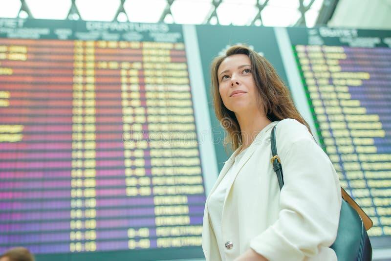 Giovane donna in aeroporto internazionale che esamina il bordo di informazioni di volo che controlla per vedere se c'è il volo immagine stock libera da diritti