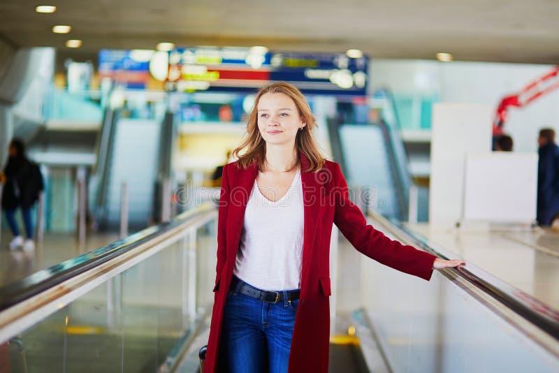 Giovane donna in aeroporto internazionale con bagagli immagine stock libera da diritti