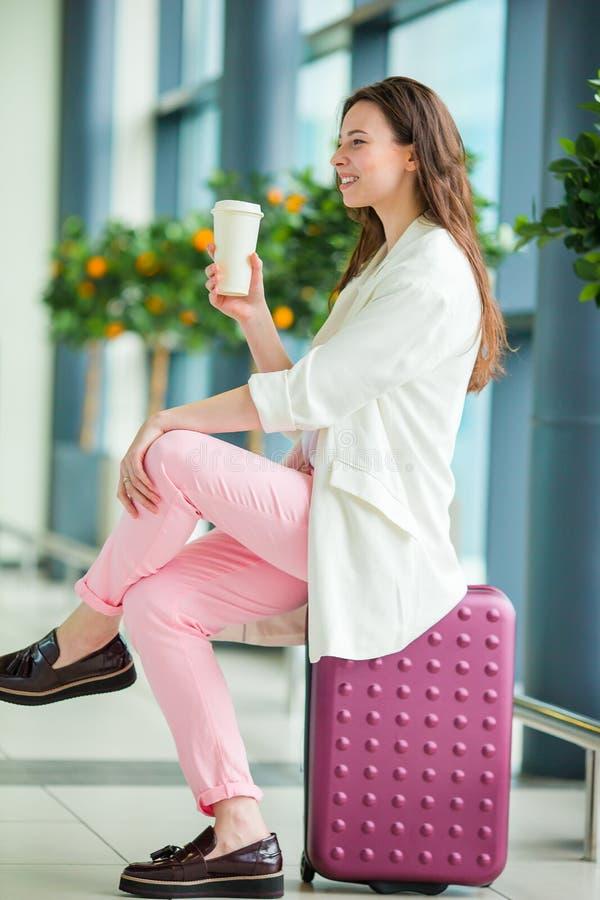 Giovane donna in aeroporto internazionale con i suoi bagagli e caffè da andare aspettare il suo volo immagini stock