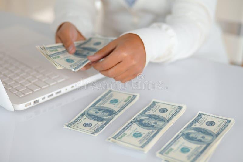 Giovane donna affascinante che conta denaro contante fotografia stock