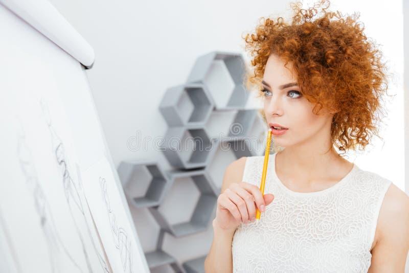 Giovane donna affascinante pensierosa della testarossa che fa gli schizzi fotografie stock libere da diritti