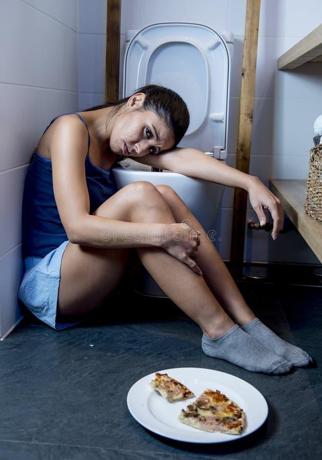 Giovane donna affetta da bulimia triste e depressa che ritiene colpevole malato dopo il vomito della pizza nella toilette del WC immagini stock libere da diritti