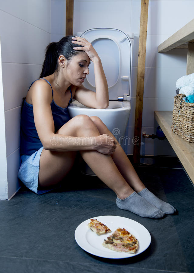 Giovane donna affetta da bulimia triste e depressa che ritiene colpevole malato dopo il vomito della pizza nella toilette del WC immagini stock