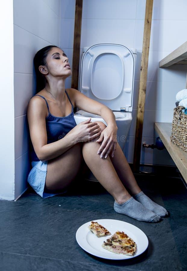 Giovane donna affetta da bulimia triste e depressa che ritiene colpevole malato dopo il vomito della pizza nella toilette del WC fotografia stock libera da diritti