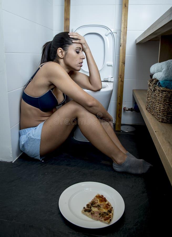Giovane donna affetta da bulimia triste e depressa che ritiene colpevole malato dopo il vomito della pizza nella toilette del WC fotografia stock