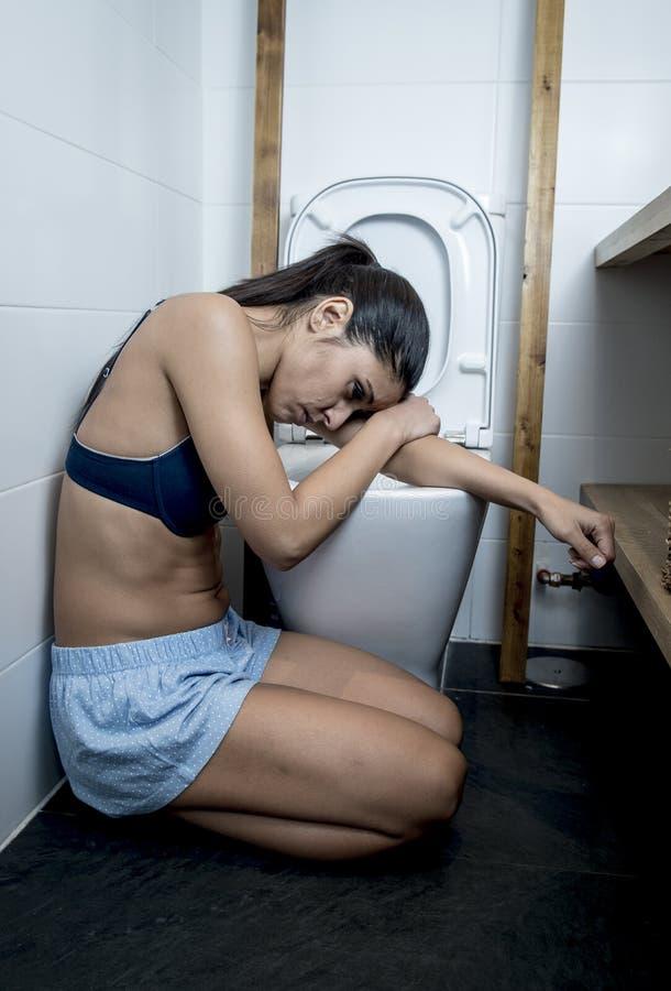 Giovane donna affetta da bulimia triste e depressa che ritiene seduta malata al pavimento della toilette che si appoggia WC fotografia stock