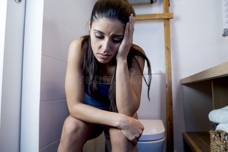 Giovane donna affetta da bulimia triste e depressa che ritiene seduta malata nel WC della toilette che sembra disperato e malato fotografie stock