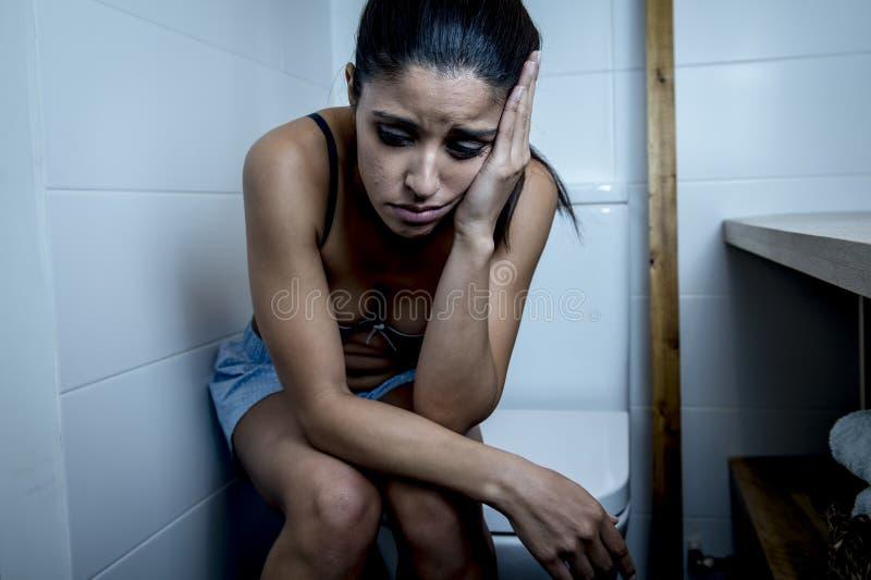 Giovane donna affetta da bulimia triste e depressa che ritiene seduta malata nel WC della toilette che sembra disperato e malato immagine stock