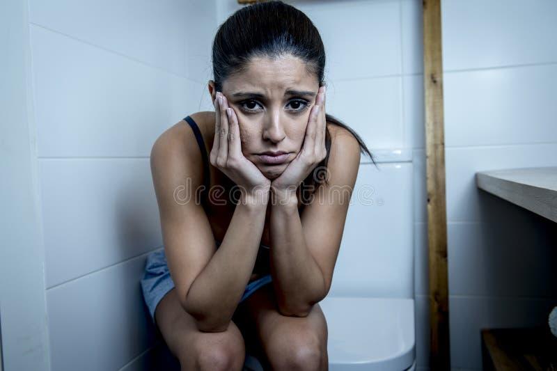 Giovane donna affetta da bulimia triste e depressa che ritiene seduta malata nel WC della toilette che sembra disperato e malato immagini stock