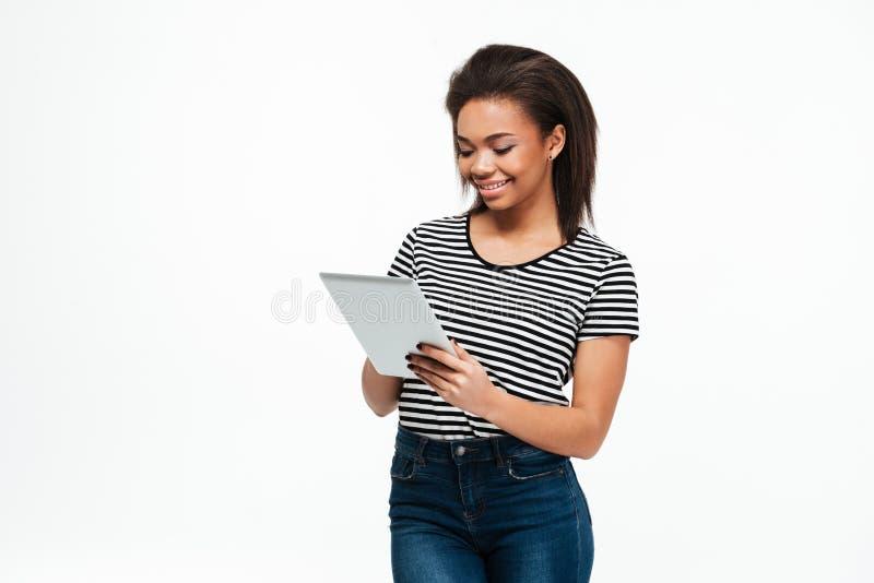Giovane donna africana allegra che per mezzo del computer della compressa immagine stock libera da diritti