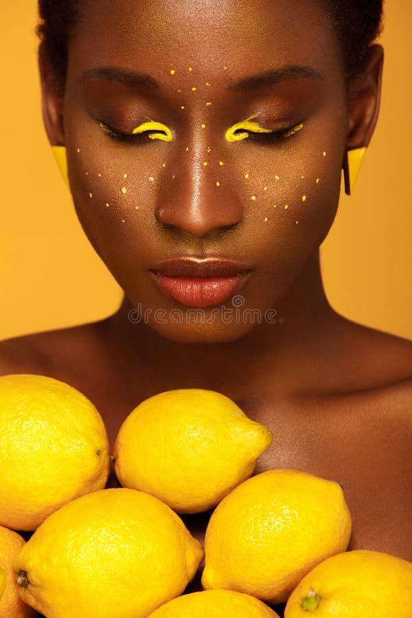 Giovane donna africana allegra con trucco giallo su lei occhi Modello femminile contro fondo giallo con i limoni gialli fotografia stock libera da diritti