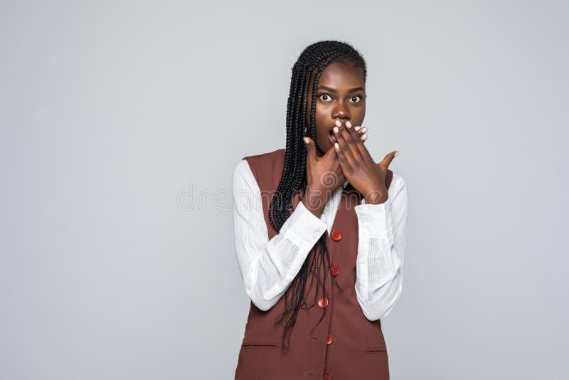 Giovane donna africana colpita che copre la sua bocca e che esamina la macchina fotografica sopra fondo grigio fotografie stock
