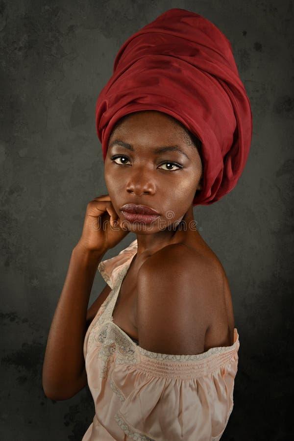 Giovane donna africana con il turbante rosso immagine stock