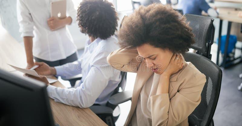 Giovane donna africana di affari che ha sforzo ed emicrania nell'ufficio immagine stock