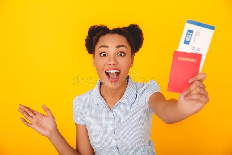 Giovane donna africana isolata sul passaporto di concetto del viaggiatore di stile dello studio giallo della parete e sul primo p fotografia stock libera da diritti