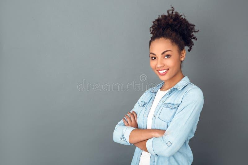 Giovane donna africana isolata sullo stile di vita quotidiano casuale dello studio grigio della parete sicuro fotografia stock libera da diritti