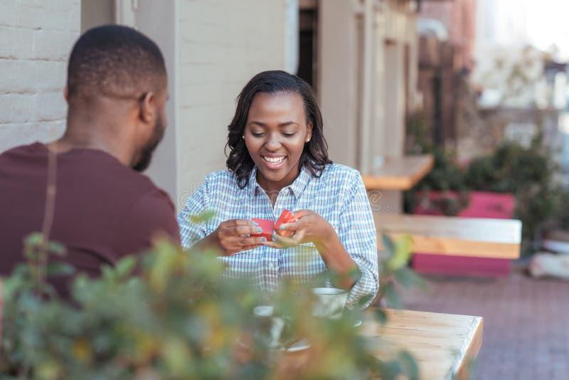 Giovane donna africana sorridente che apre un presente dal suo ragazzo fotografia stock