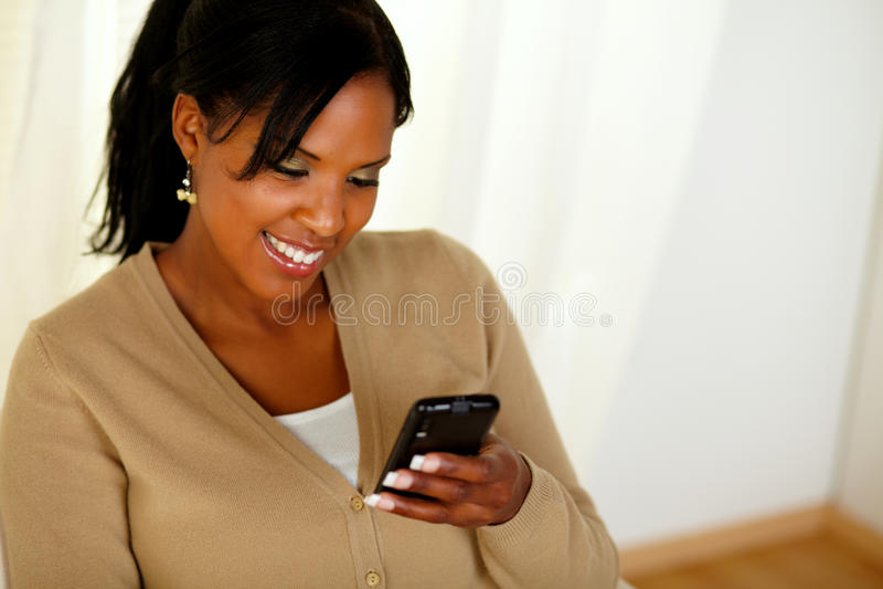 Giovane donna afro-american che legge un messaggio immagini stock