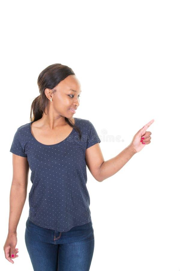 Giovane donna afroamericana in abbigliamento blu casuale che indica dito via da parte sopra il fondo bianco fotografie stock