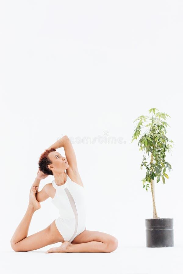 Giovane donna afroamericana attraente che fa allungando gli esercizi di yoga immagini stock libere da diritti