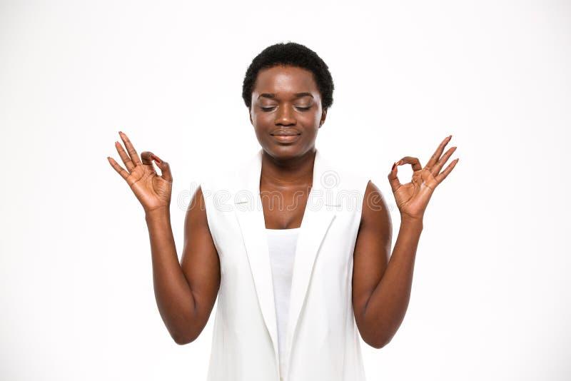 Giovane donna afroamericana attraente pacifica che medita e che tiene calma immagine stock libera da diritti
