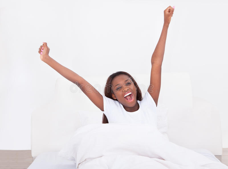 Giovane donna afroamericana che allunga a letto a casa immagini stock