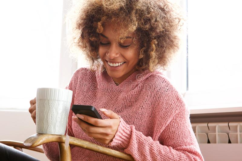 Giovane donna afroamericana che beve tazza di caffè calda e che esamina cellulare immagini stock