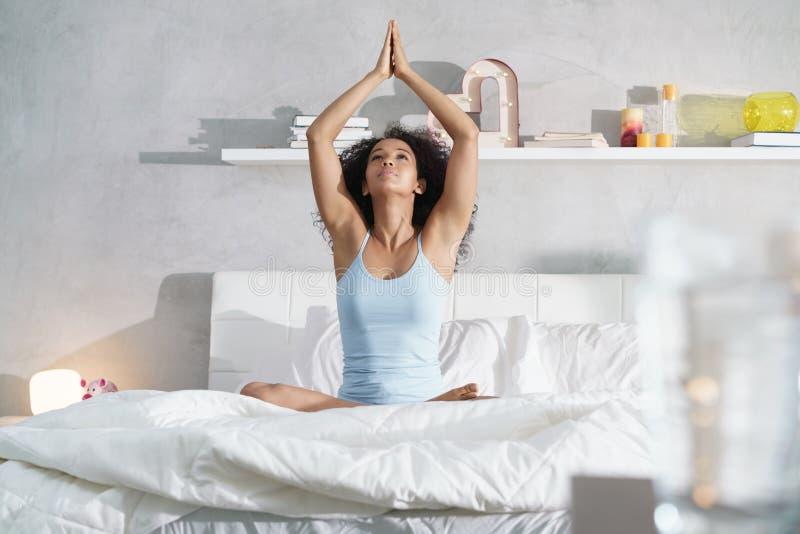 Giovane donna afroamericana che fa yoga a letto dopo il sonno immagine stock
