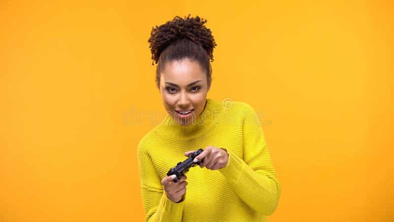 Giovane donna afroamericana che gioca i video giochi con il regolatore del gioco, divertimento fotografia stock